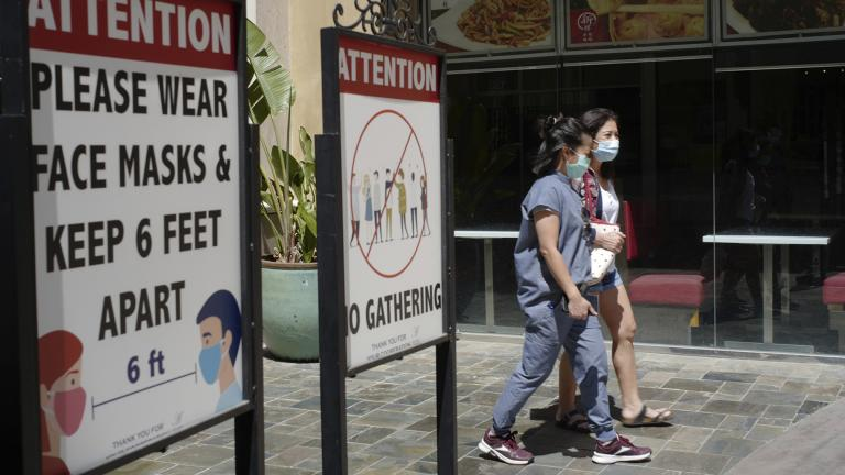 In this June 11, 2021, file photo, customers wear face masks in an outdoor mall with closed business amid the COVID-19 pandemic in Los Angeles. (AP Photo / Damian Dovarganes, File)