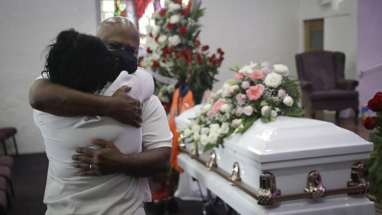 In this July 21, 2020, file photo, Darryl Hutchinson, facing camera, is hugged by a relative during a funeral service for Lydia Nunez, who was Hutchinson's cousin at the Metropolitan Baptist Church in Los Angeles. Nunez died from COVID-19. (AP Photo / Marcio Jose Sanchez, File)