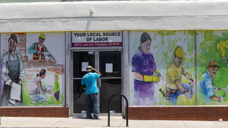 In this May 7, 2020, file photo, a person looks inside the closed doors of the Pasadena Community Job Center in Pasadena, Calif., during the coronavirus outbreak. (AP Photo/Damian Dovarganes, File)