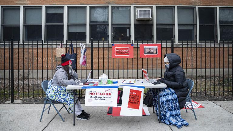 In this Monday, Jan. 11, 2021 file photo, teachers Adrienne Thomas, left, and Irene Barrera, right set up their computers and materials for their virtual classes outside of Suder Montessori Magnet Elementary School in solidarity with pre-K educators forced back into the building in Chicago. (Anthony Vazquez / Chicago Sun-Times via AP, File)
