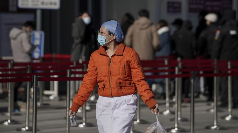A nurse wearing a face mask to help curb the spread of the coronavirus walks by people lining up for a coronavirus test at a hospital in Beijing, Sunday, Jan. 17, 2021. (AP Photo / Andy Wong)