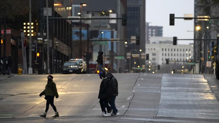 Pedestrians wear masks while crossing an empty road at the intersection of Market Street and 15th Avenue during the evening rush hour Monday, Dec. 28, 2020, in downtown Denver. (AP Photo / David Zalubowski)