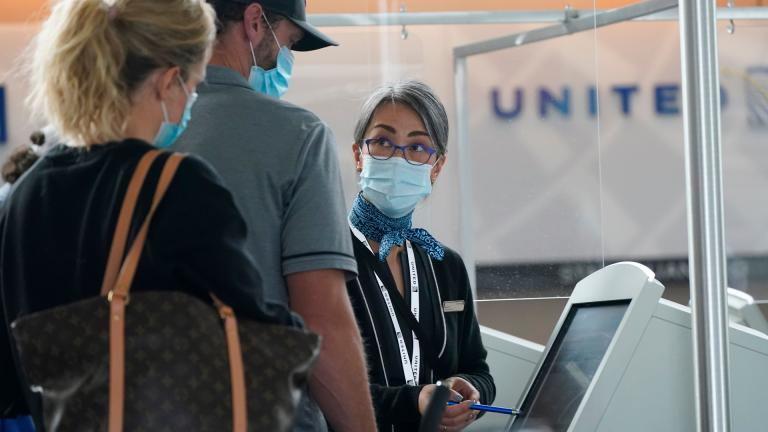 Travelers check in at a United Airlines kiosk with help from a United employee in the main terminal of Denver International Airport Thursday, Oct. 1, 2020, in Denver. (AP Photo / David Zalubowski)
