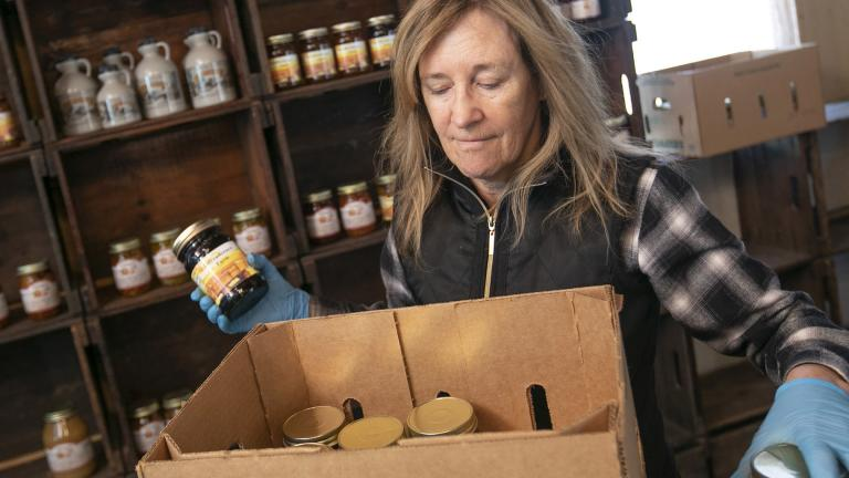 Linda DeFrancesco stocks shelves with her farm's own salsa, spreads, veggies and salsa at DeFrancesco Farm Stand in Northford, Conn., Thursday, March 26, 2020. (Dave Zajac / Record-Journal via AP)