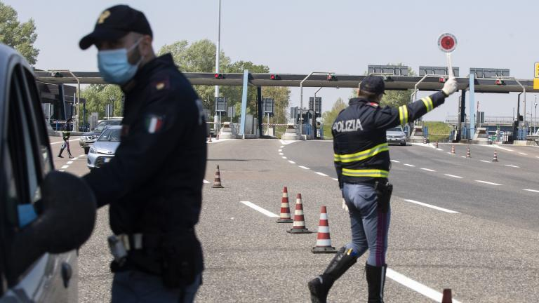 Police officers stop cars at the Melegnano highway barrier entrance, near Milan, Italy, Saturday, April 11, 2020. Using helicopters, drones and stepped-up police checks to make sure Italians don't slip out of their homes for the Easter holiday weekend, Italian authorities are doubling down on their crackdown against violators of the nationwide lockdown decree. (AP Photo/Luca Bruno)