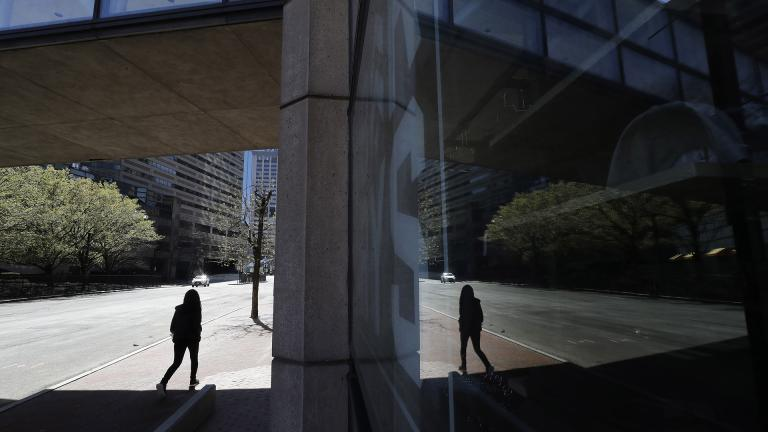 A person walks along a nearly empty street Wednesday, April 29, 2020, in Boston. Job cuts have escalated across the U.S. economy in recent days that remains all but shut down due measures taken to halt the spread of the virus. (AP Photo / Steven Senne)