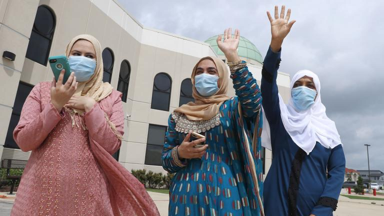 Saba Mahjabeen, right, and Gizman Mawi, center, waive as Sophia Baig looks on during a drive through Eid al-Fitr celebration outside a closed mosque in Plano, Texas, Sunday, May 24, 2020. (AP Photo / LM Otero)