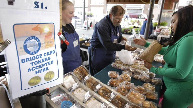 In a Sept. 11, 2010, file photo, Temeka Williams, right, of Detroit, uses her bridge card tokens for a purchase from Elizabeth and Gary Lauber from Sweet Delights at the Farmer's Market in Detroit. Farmers, growers and operators of open-air markets are heading into a busy time of the year, in early May 2020, as many states still are under stay-at-home orders for residents and non-essential businesses to slow the spread of the new coronavirus. (AP Photo/Carlos Osorio, File)