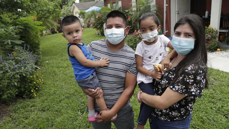 In this Sunday, June 7, 2020, photo, Elbin Sales, second from left, poses for a photograph with his wife, Yecenia Solorzano, right, and children Jordi Sales, left, and Athena Sales, amid the new coronavirus pandemic in Immokalee, Fla. (AP Photo / Lynne Sladky)