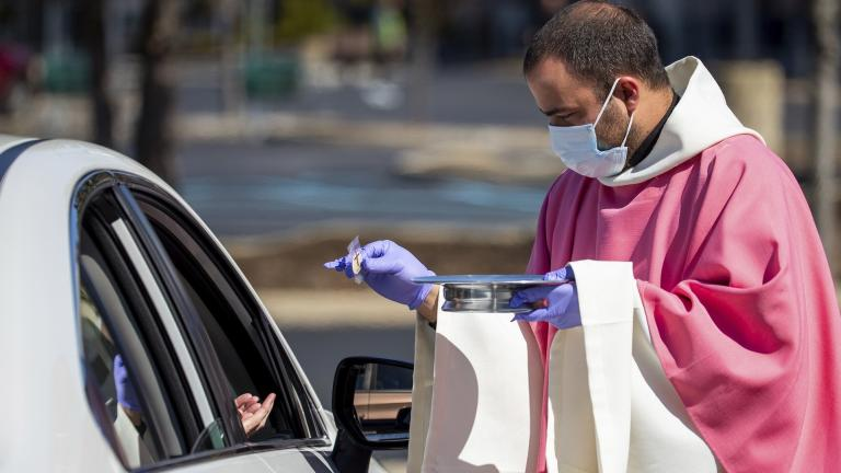 In this Sunday, March 22, 2020 file photo, the Rev. William A. Mentz, pastor of the Scranton, Pa.-based St. Francis and Clare Progressive Catholic Church, wears a mask and gloves while distributing prepackaged communion to the faithful attending Mass while sitting in their cars in the parking lot of a shopping center in Moosic, Pa. (Christopher Dolan/The Times-Tribune via AP)
