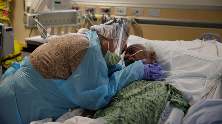 In this July 31, 2020, file photo, Romelia Navarro, 64, weeps while hugging her husband, Antonio, in his final moments in a COVID-19 unit at St. Jude Medical Center in Fullerton, Calif. (AP Photo / Jae C. Hong, File)