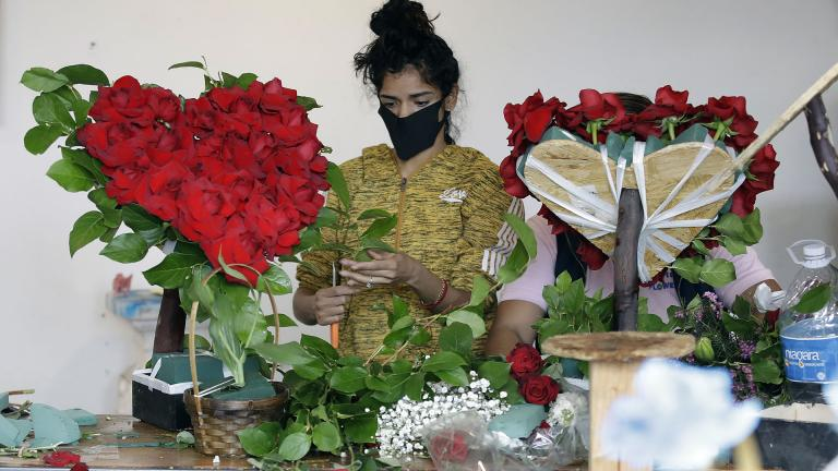In this May 10, 2020, file photo, a merchant prepares a floral arrangement on Mother's Day at the Los Angeles Flower Market in Los Angeles. (AP Photo / Marcio Jose Sanchez, File)