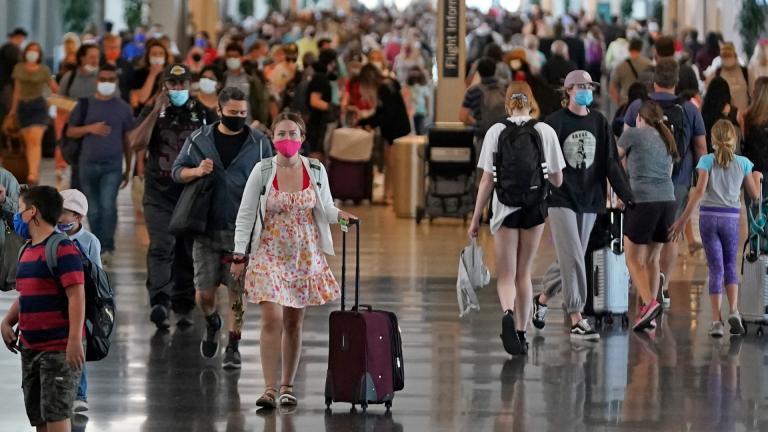 In this July 1, 2021, file photo, people walk through Salt Lake City International Airport in Salt Lake City. (AP Photo / Rick Bowmer, File)