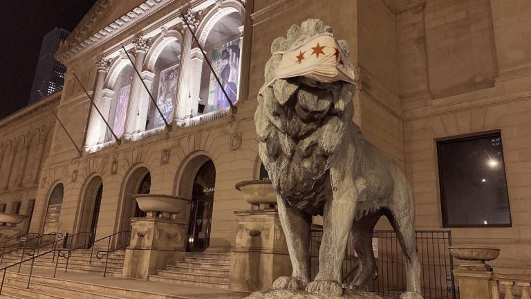 This Friday, May 1, 2020 photo shows a lion statue with a mask placed on it at the Art Institute of Chicago. (Sam Kelly / Chicago Sun-Times via AP)