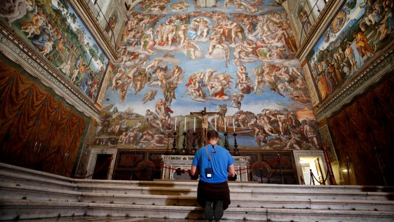 A visitor kneels in front of the Last Judgement fresco by the Italian Renaissance painter Michelangelo inside the Sistine Chapel of the Vatican Museums on the occasion of the museum's reopening, in Rome, Monday, May 3, 2021. The Vatican Museums reopened Monday to visitors after a shutdown following COVID-19 containment measures. (AP Photo / Alessandra Tarantino)