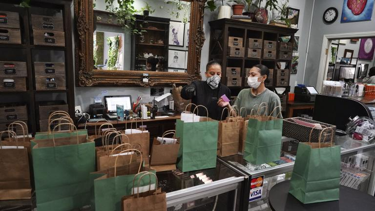 In this Thursday, April 16, 2020, photo, wearing a protective mask and gloves, budtenders prepare orders for customers to pick-up at The Higher Path cannabis dispensary in the Sherman Oaks section of Los Angeles. (AP Photo / Richard Vogel)