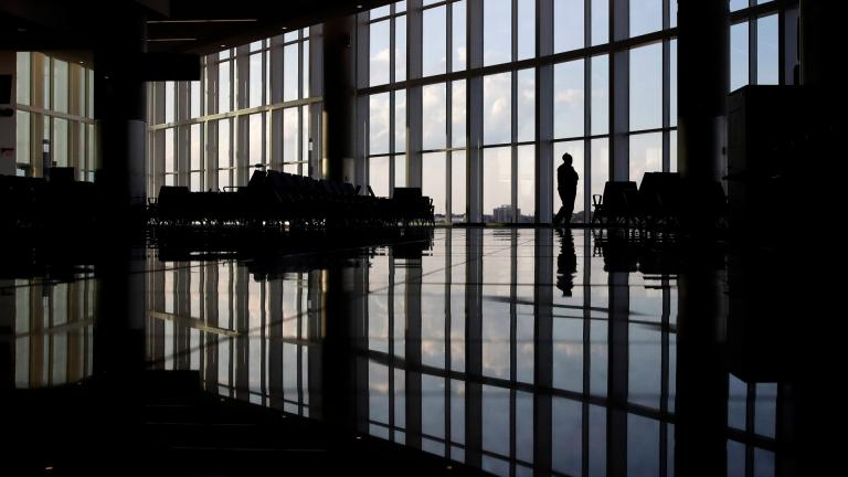 In this Monday, June 1, 2020 file photo, a woman looks through a window at a near-empty terminal at an airport in Atlanta. (AP Photo / Charlie Riedel)