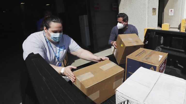 Christina Caldwell, left, of Henry Ford Population Health helps unload supplies with Matt Thatcher, who donated them from the Detroit Golf Club, Wednesday, April 8, 2020, in Detroit. (AP Photo / Carlos Osorio)