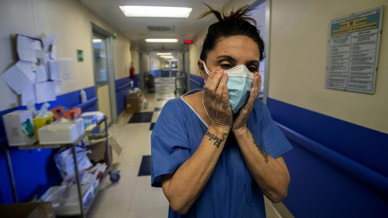 In this April 10, 2020, file photo, nurse Cristina Settembrese fixes two masks to her face during her work shift in the COVID-19 ward at the San Paolo hospital in Milan, Italy. (AP Photo / Luca Bruno, File)