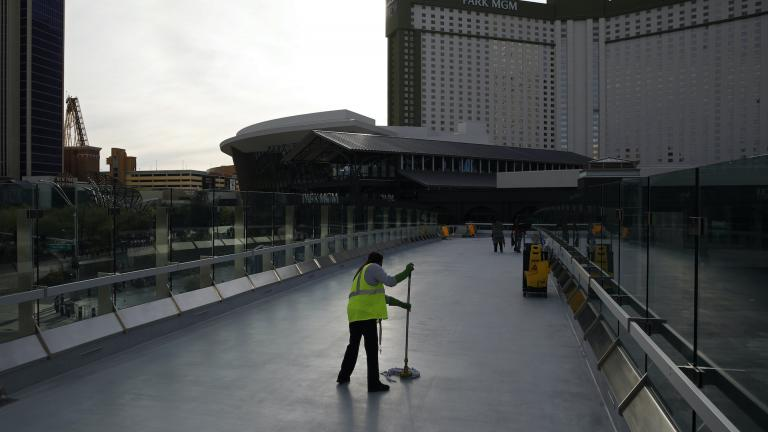 In this March 31, 2020, file photo, a worker cleans along the Las Vegas Strip devoid of the usual crowds as casinos and other business are shuttered due to the coronavirus outbreak in Las Vegas. (AP Photo/John Locher, File)