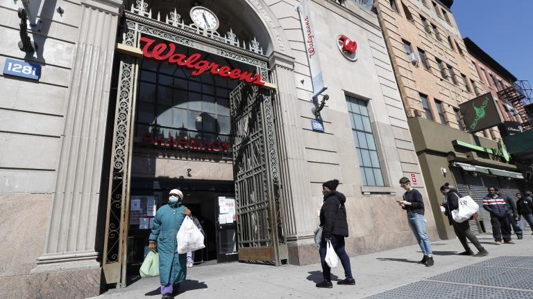 In this March 26, 2020 file photo, a woman leaves a Walgreens pharmacy that is enforcing social distancing rules by allowing only a certain numbers of people in as customers line up on the sidewalk outside the store in New York. The coronavirus pandemic pushed the drugstore chain to a $1.7-billion loss in its fiscal third quarter, as customers stayed home to avoid the virus or consolidated their shopping to grocery stores. (AP Photo/Kathy Willens, File)