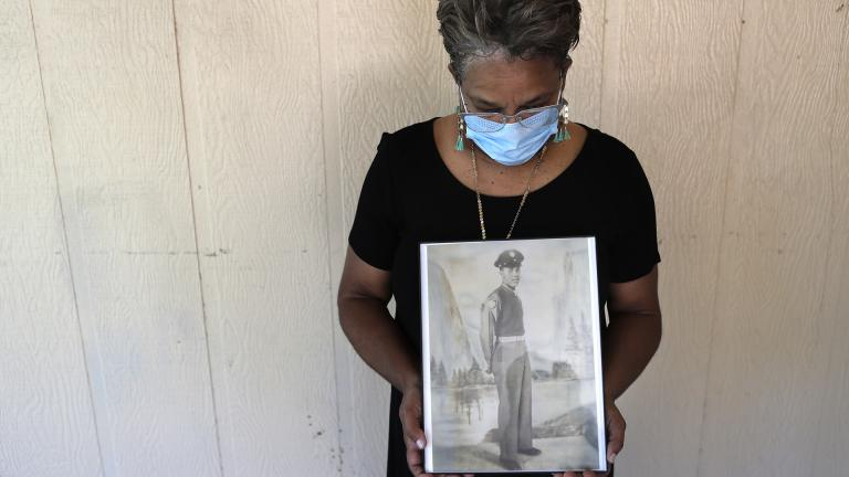 In this May 18, 2020, file photo, Belvin Jefferson White poses with a portrait of her father Saymon Jefferson at Saymon's home in Baton Rouge, La. Belvin recently lost both her father and her uncle, Willie Lee Jefferson, to COVID-19.  (AP Photo/  Gerald Herbert, File)