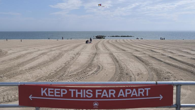 In this April 12, 2020, file photo, a sign on the Coney Island boardwalk reminds people to keep their distance in New York. (AP Photo / Seth Wenig, File)