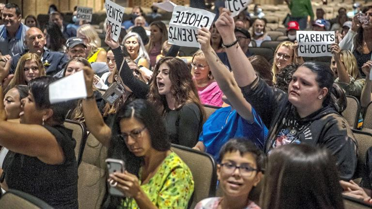 In this Aug. 25, 2021 file photo, people hold signs and chant during a meeting of the North Allegheny School District school board regarding the district's mask policy, at at North Allegheny Senior High School in McCandless, Pa. (Alexandra Wimley/Pittsburgh Post-Gazette via AP, File)