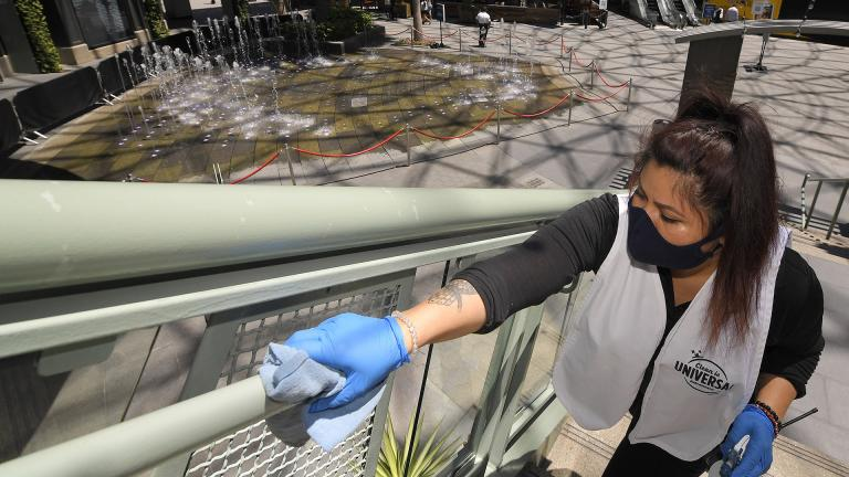 In this Thursday, June 11, 2020 file photo, Andrea Castaneda cleans the railings at Universal CityWalk near Universal City, California. (AP Photo / Mark J. Terrill)