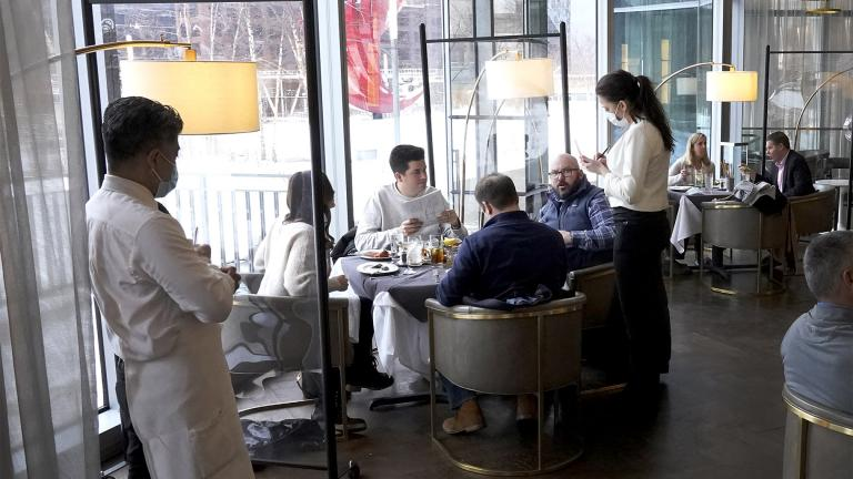 """In this Jan. 27, 2021 file photo, patrons enjoy lunch indoors at Gibsons Italia restaurant in Chicago. A recent spike in coronavirus cases in some states has led one of the nation's top health experts to suggest that governors could """"close things down"""" like they did during previous surges. But that doesn't appear likely to happen — not even in states led by Democratic governors who favored greater restrictions in the past. (AP Photo / Charles Rex Arbogast, File)"""