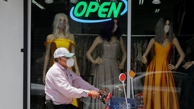 In this July 30, 2020, file photo, a cyclist passes a display window with mask covered mannequins at a dress store in McAllen, Texas. (AP Photo / Eric Gay, File)