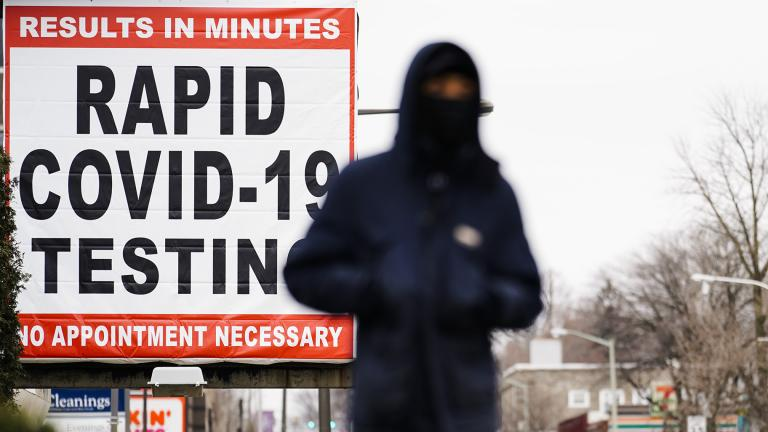 In this Jan. 25, 2021, file photo, a person wearing face mask as a precaution against the coronavirus walks near a sign advertising a rapid COVID-19 testing site in Philadelphia. (AP Photo / Matt Rourke, File)