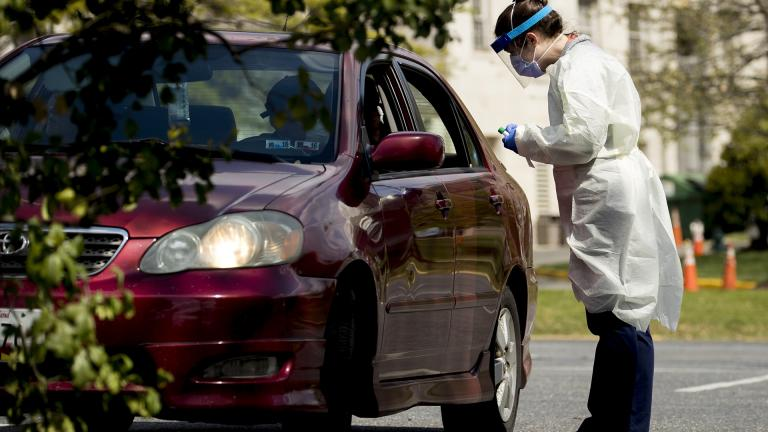 A medical worker prepares to test a young man for COVID-19 at a Children's National Hospital drive-through coronavirus testing site at Trinity University, Thursday, April 16, 2020, in Washington. (AP Photo / Andrew Harnik)