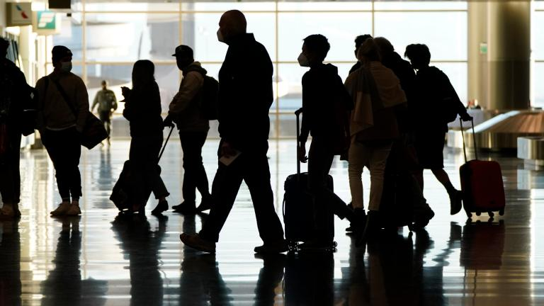 In this Nov. 25, 2020, file photo, air travelers line up to go through a a security checkpoint at Salt Lake City International Airport in Salt Lake City. (AP Photo / Rick Bowmer, File)