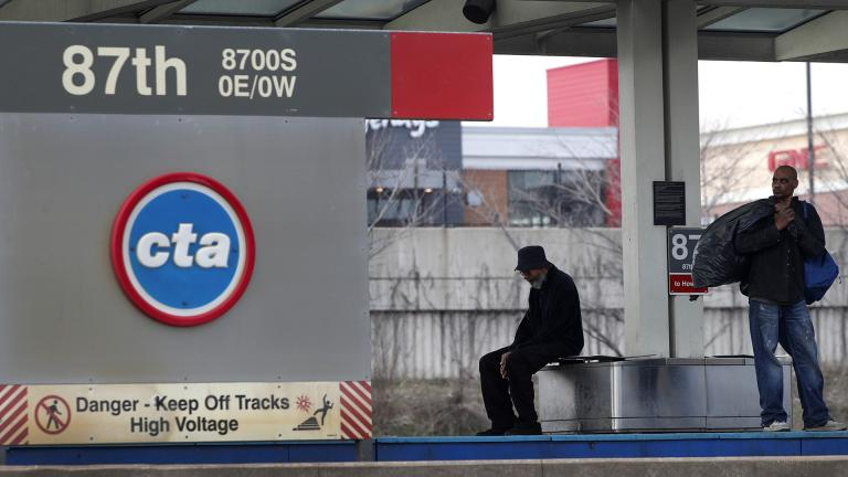 In this April 7, 2020, file photo, two men wait for a Chicago Transit Authority Red Line train on Chicago's South Side. (AP Photo / Charles Rex Arbogast, File)