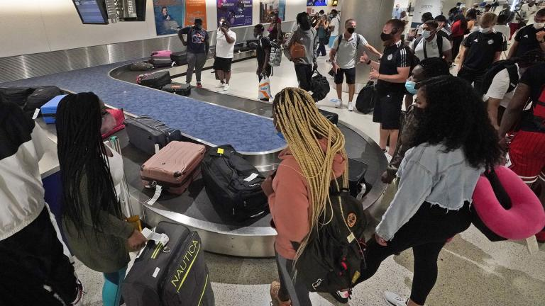 In this May 28, 2021 file photo, travelers wait for their luggage at a baggage carousel at Miami International Airport in Miami. (AP Photo / Wilfredo Lee, File)