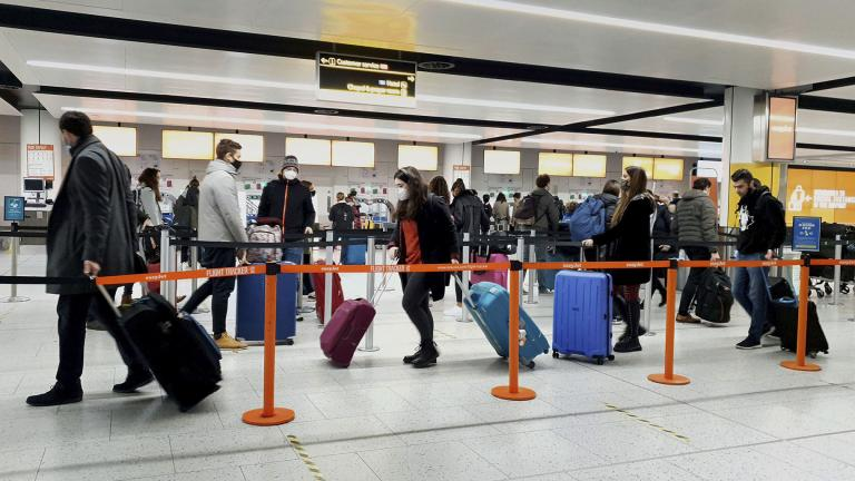 In this Dec. 20, 2020, file photo, passengers queue for check-in at Gatwick Airport in West Sussex, England, south of London. (Gareth Fuller / PA via AP)