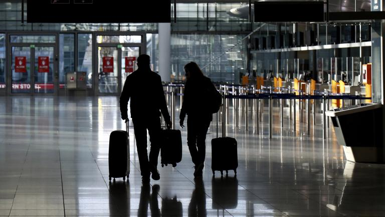 In this Saturday, Dec. 26, 2020 file photo, people walk with their luggage through a deserted check-in hall at the airport in Munich, Germany as Germany continues its second lockdown to avoid the further outspread of the coronavirus. (AP Photo / Matthias Schrader)