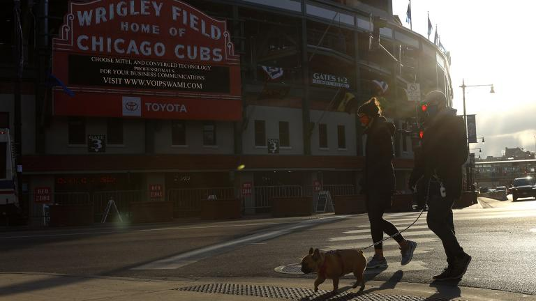 People walk their dog outside of Wrigley Field on opening day for the Chicago Cubs, Thursday, April 1, 2021, in Chicago. (AP Photo / Shafkat Anowar)