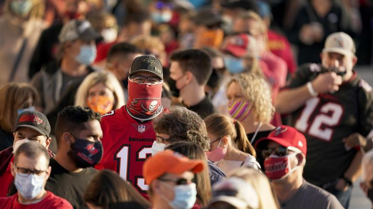 In this Feb. 4, 2021, file photo, people wait in line for an exhibit at the NFL Experience in Tampa, Fla. (AP Photo / Charlie Riedel, File)