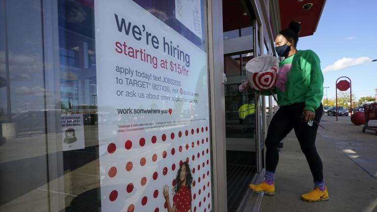 In this Sept. 30, 2020, file photo, a passerby walks past a hiring sign while entering a Target store in Westwood, Mass. (AP Photo/Steven Senne, File)