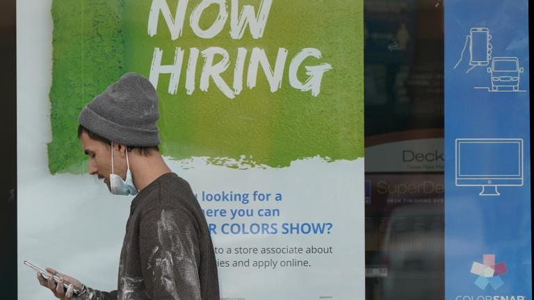 "A man walks past a ""Now Hiring"" sign on a window at Sherwin Williams store, Friday, Feb. 26, 2021, in Woodmere Village, Ohio. (AP Photo / Tony Dejak)"