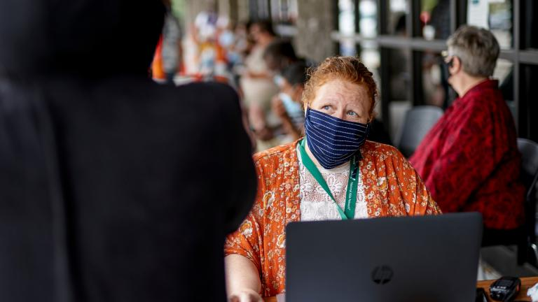 In this July 15, 2020, file photo, One-stop operator Vickie Gregorio with the Heartland Workforce Solutions talks to a jobseeker outside the workforce office in Omaha, Neb., as others seeking employment wait behind her. (AP Photo / Nati Harnik, File)