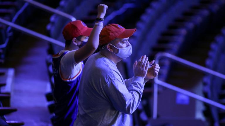 Fans cheer the New York Knicks coming out to warm up for an NBA basketball game against the Golden State Warriors on Tuesday, Feb. 23, 2021, in New York. A limited number of fans were allowed to attend. (Wendell Cruz / Pool Photo via AP)