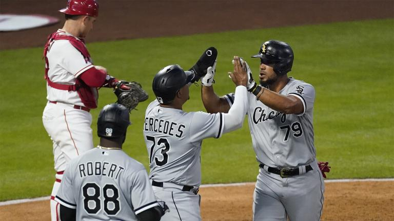 Chicago White Sox's Jose Abreu (79) high-fives Yermin Mercedes (73) after hitting a grand slam during the third inning of an MLB baseball game against the Los Angeles Angels Friday, April 2, 2021, in Anaheim, Calif. Mercedes, Tim Anderson, and Luis Robert (88) also scored. (AP Photo / Ashley Landis)