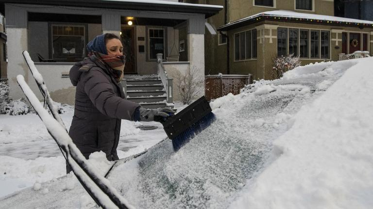 Sarah Lee clears snow off her vehicle in the Edgewater neighborhood, after a snowstorm in Chicago, Tuesday, Jan. 26, 2021. (Tyler LaRiviere / Chicago Sun-Times via AP)