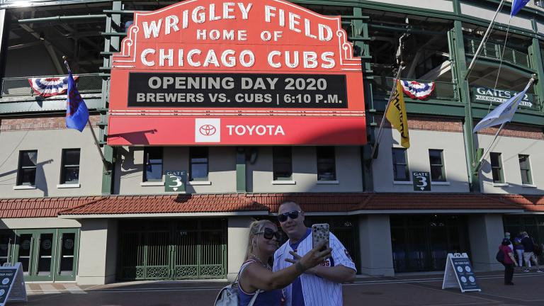 Sandra Bilger, left, and Dustin Moore take a photo in front of the marquee at Wrigley Field before an opening day baseball game between the Chicago Cubs and the Milwaukee Brewers in Chicago, Friday, July 24, 2020, in Chicago. (AP Photo / Nam Y. Huh)