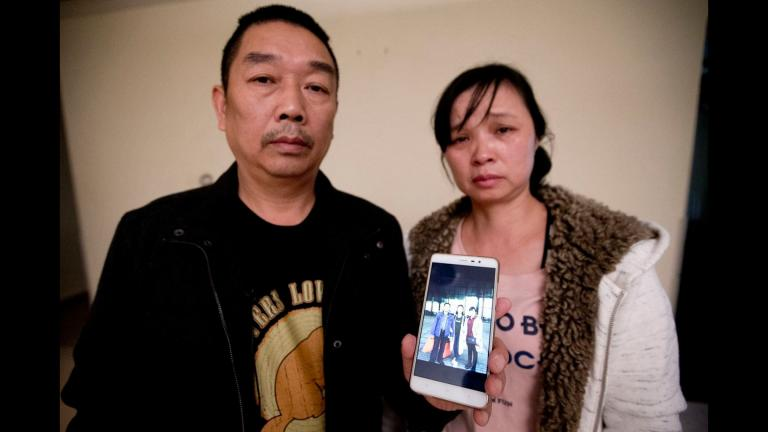 Ronggao Zhang, left, and Lifeng Ye display a photo of them with their missing daughter, Yingying Zhang, in this Nov. 1, 2017 file photo. They have now returned to Illinois as the trial of the man accused in her disappearance is set to begin June 3, 2019. (Michael Conroy File / Associated Press)