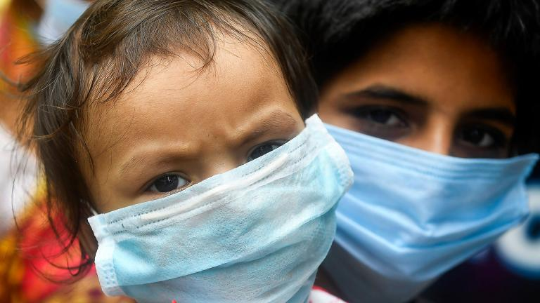 Children wearing face masks wait in a queue with others to take swab samples to test for the COVID-19 coronavirus, in Kolkata on July 28, 2020. (DIBYANGSHU SARKAR / AFP / AFP via Getty Images)