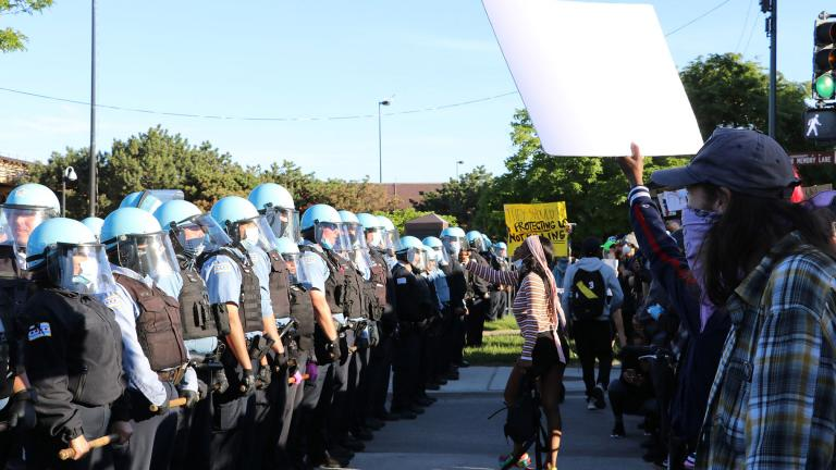 Protesters yell at a line of police officers at State and 35th streets, about 3 miles south of the Loop, where police set up a blockade on Sunday, May 31, 2020. (Evan Garcia / WTTW News)